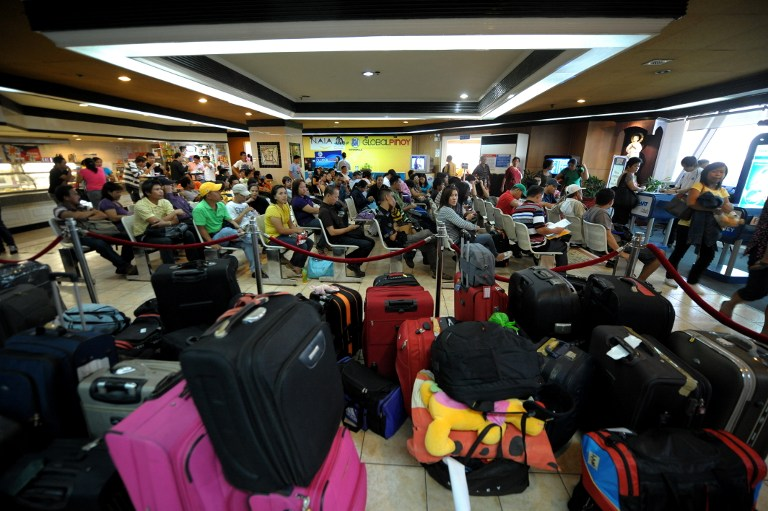 ILLEGAL RECRUITMENT. Some overseas Filipino workers fall into the trap of illegal recruiters due to the government's slow processing of their documents. File photo by Noel Celis/AFP