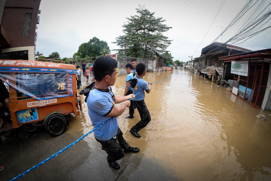 RESCUE OPERATIONS. Police field trainees pull ropes used to connect to rescued residents in Makahambus Street in Cagayan de Oro City as Tropical Storm Vinta lashes Northern Mindanao on Friday, December 22, 2017. Photo by Bobby Lagsa/Rappler