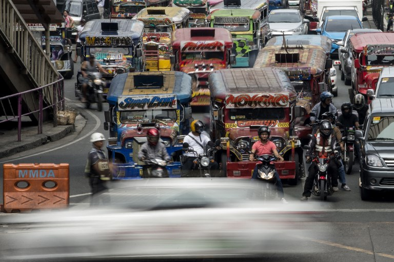 PUV MODERNIZATION. Jeepneys are seen as an enforcer manages traffic at a busy street in Manila on May 30, 2017. Photo from Agence France-Presse