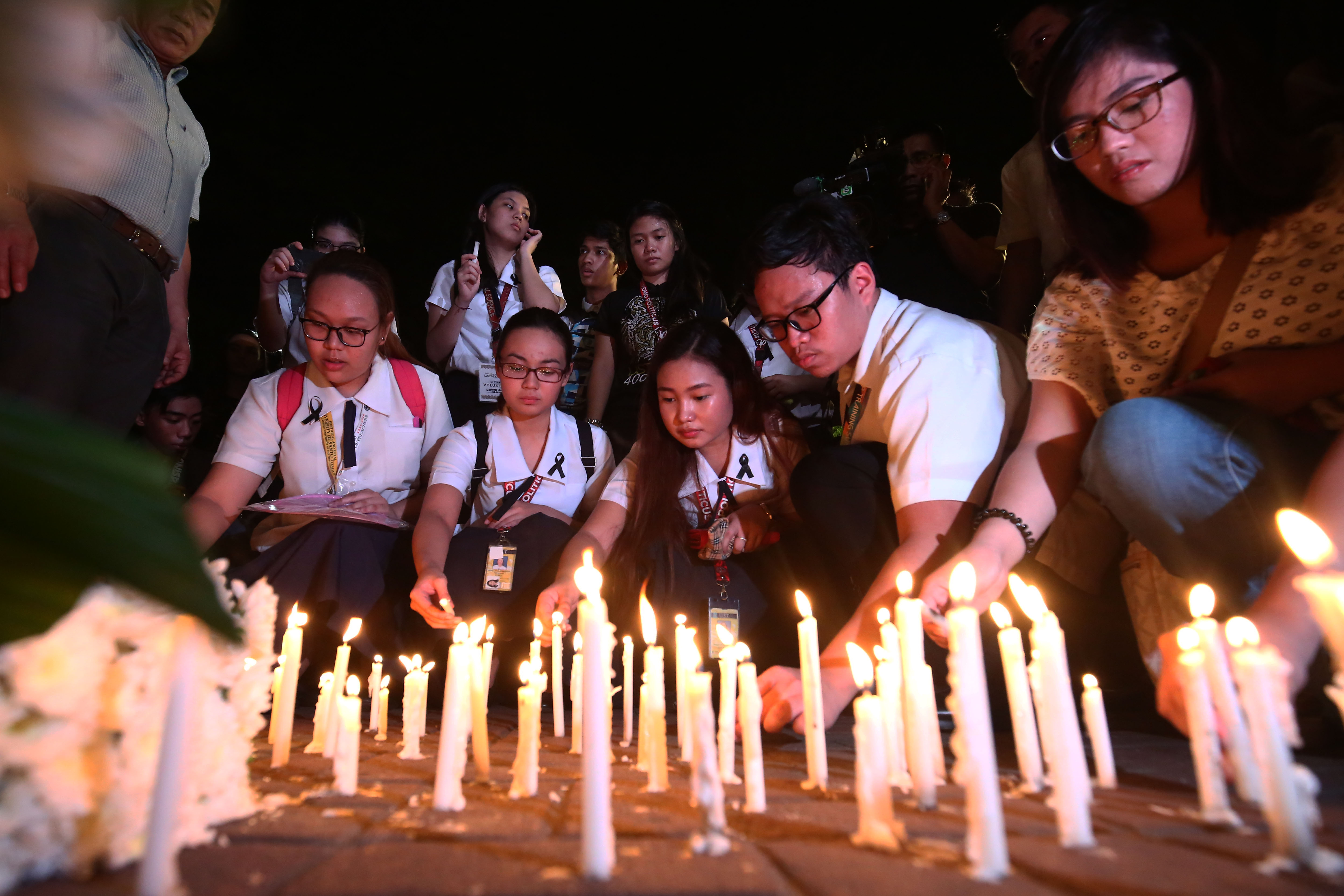 PRAYERS FOR A SCHOOLMATE. Students and faculty light candles as they offer a prayer for schoolmate Horacio Castillo III in front of the Faculty of Civil Law inside the UST campus in Manila on September 18, 2017. Photo by Ben Nabong/ Rappler