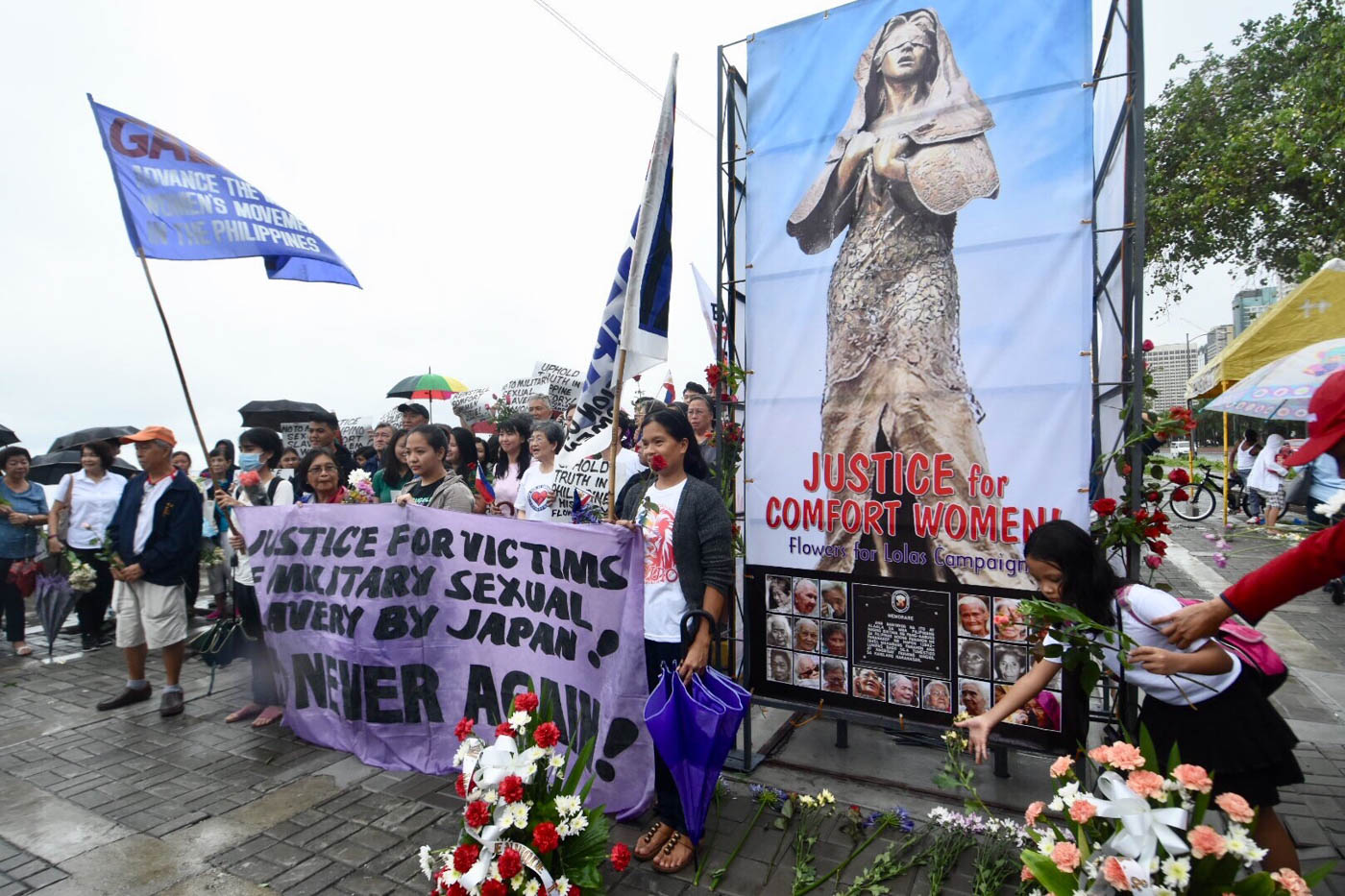 THE MISSING STATUE. Women gathered at where the statue was once erect, along the baywalk of Roxas Boulevard, Manila. Photo by Angie de Silva/Rappler
