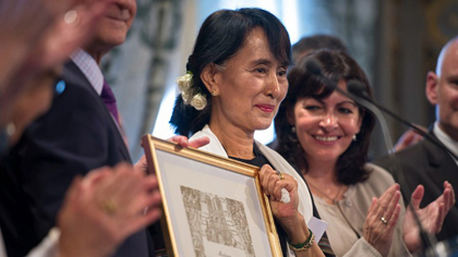 Myanmar pro-democracy leader Aung San Suu Kyi (C) poses after receiving an honorary citizen award, beside Paris' deputy mayor Anne Hidalgo (R) at the Paris City Hall on June 27, 2012. AFP PHOTO / FRED DUFOUR
