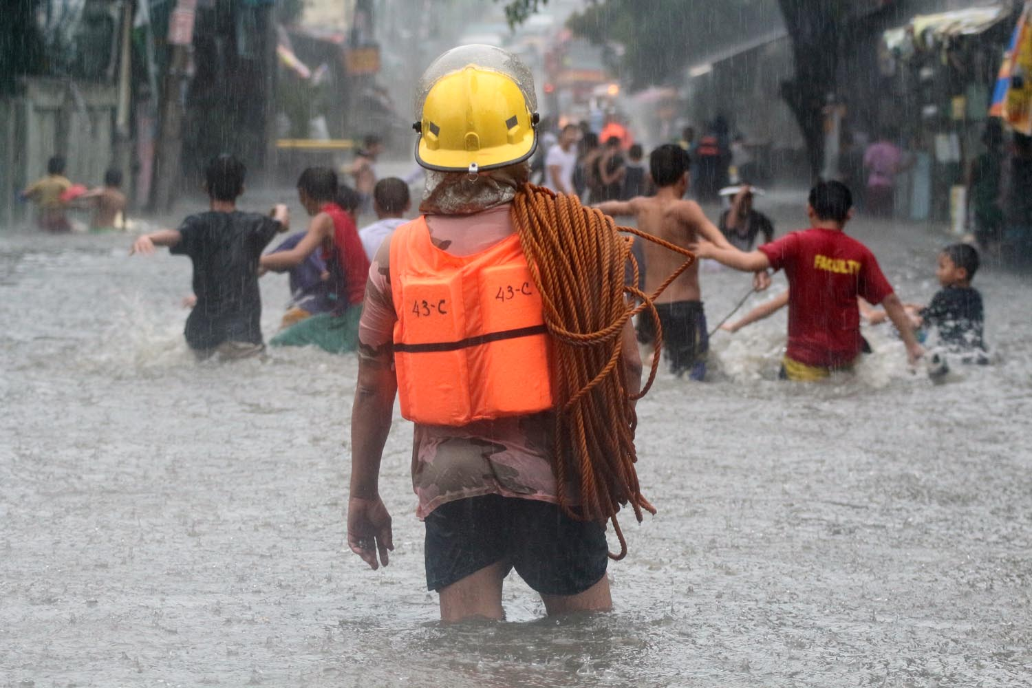 FLOODWATER. Children wade through waist-deep floodwater caused by monsoon rains along AFP Road in Quezon City. Photo by Joel Liporada/Rappler