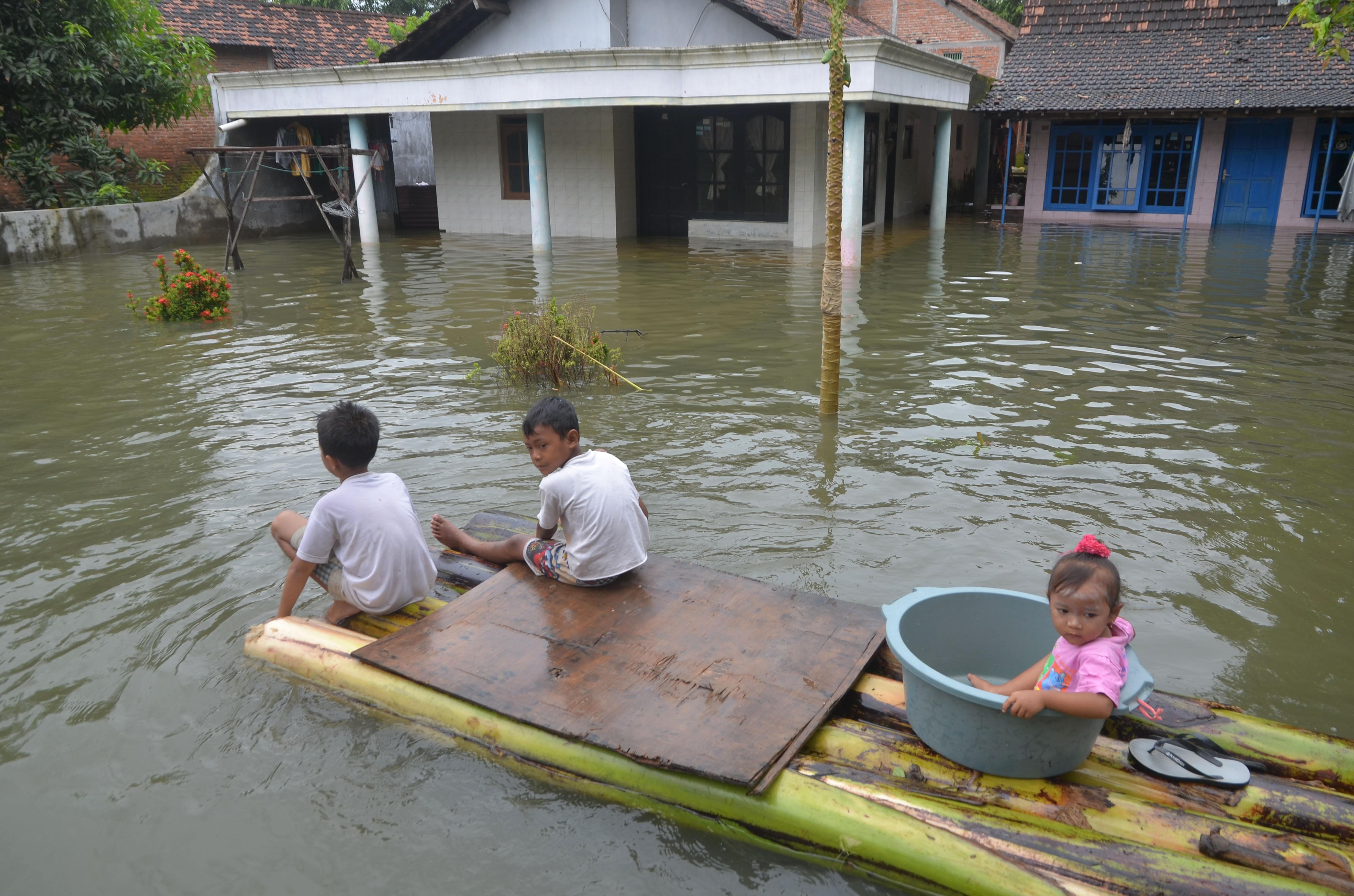 Anak-anak dengan menggunakan rakit batang pisang melewati jalan yang tergenang banjir di Desa Jati Wetan, Kudus, Jawa Tengah, pada 9 Februari 2017. Foto oleh Yusuf Nugroho/Antara