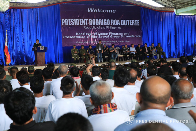 GOVERNMENT AID. President Rodrigo Duterte tells Abu SAyyaf surrenderers that the government will help them get back on their feet during the presentation of firearms they turned over to the military in Patikul, Sulu, on March 26, 2018. Presidential Photo