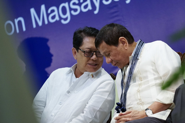 CHALLENGE TO REDS. President Rodrigo Duterte sits beside Labor Secretary and peace panel chief Bebot Bello during the SSS anniversary. Presidential photo