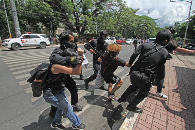 ARRESTED. Police drag two activists who joined an anti-terrorism bill protest in front of the gfate of University of the Philippines Cebu campus on June 5, 2020. Police say they violated the rule on mass gathering as Cebu City is under general community quarantine Photo by Gelo Litonjua/Rappler