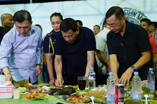 DUTERTE'S SECURITY TEAM. President Rodrigo Duterte gets ready to dine with PSG chief Brigadier General Lope Dagoy during the 2017 Christmas party with the Presidential Security Group. Malacañang file photo