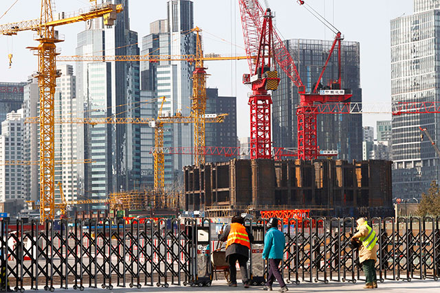 Chinese workers enter a compound of a construction site in Beijing, China, January 28, 2015. Despite a slowdown in economic growth to 7.4% in 2014 and an economic growth forecast of 6.8% issued by the International Monetary Fund for 2015, China is looking to create some 10 million new jobs in 2015 as part of measures for economic stability. EPA / ROLEX DELA PENA