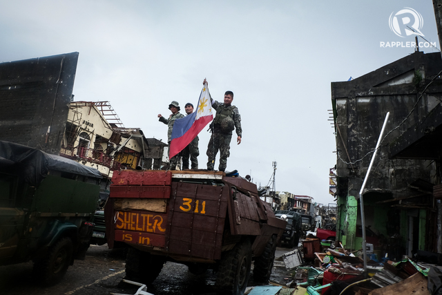 LIBERATED. Soldiers hold up a Philippine flag on October 17, 2017 on President Rodrigo Duterte's declaration of liberation of Marawi City. Photo by Bobbby Lagsa/Rappler