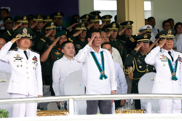 CHANGE OF COMMAND. President Rodrigo Duterte (center), retired General Eduardo Año (left), and new AFP chief Lieutenant General Rey Guerrero (right) salute to the troops during the AFP change of command ceremony at Camp Aguinaldo on October 26, 2017. Malacañang photo