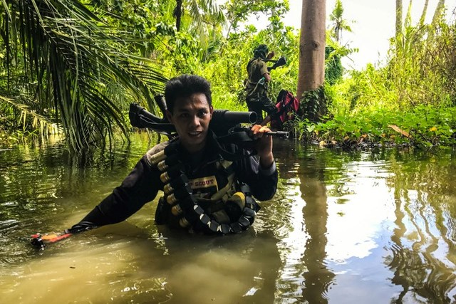 TO THE FRONT LINES. This photo taken on August 22, 2017 shows a member of the Moro Islamic Liberation Front (MILF) wading through a flooded farm on his way to the frontline in Datu Salibo town, Maguindanao province, Mindanao. Photo by  Ferdinandh Cabrera/AFP