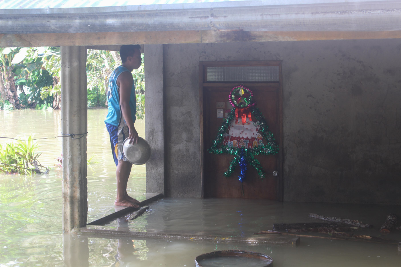 LIFE INTERRUPTED. A man armed with a basin checks his flooded home situated along the Loboc River. Photo by Michael Ortega Ligalig/Rappler