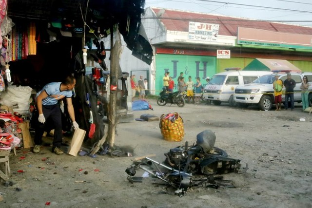 BLAST. A police investigator (left) gathers evidence at the site of a bomb blast in Isulan town on the southern island of Mindanao on August 29, 2018. File photo by AFP