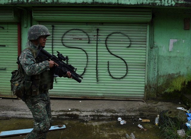 SECURITY CRISIS. A Philippine Marine walks past graffiti along a deserted street in conflict-hit Marawi City on July 22, 2017. File photo by Ted Aljibe/AFP