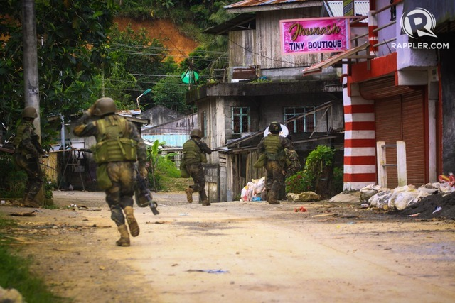 IN BATTLE. Philippine soldiers run through the streets of Marawi's main battle area. Photo by Bobby Lagsa/Rappler