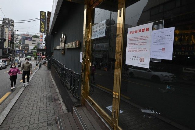 CLOSED. A couple wearing face masks walk past a nightclub, now closed following a visit by a coronavirus patient, in the popular nightlife district of Itaewon in Seoul, South Korea, on May 10, 2020. Photo by Jung Yeon-je/AFP