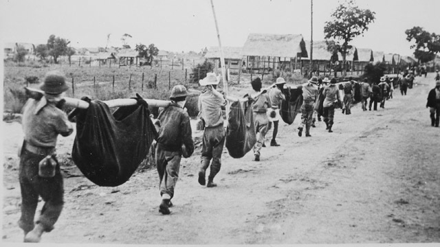 After the Bataan Death March, Allied prisoners of war carry their comrades in slings, depicting what appears to be a burial detail. File Photo from Wikimedia Commons