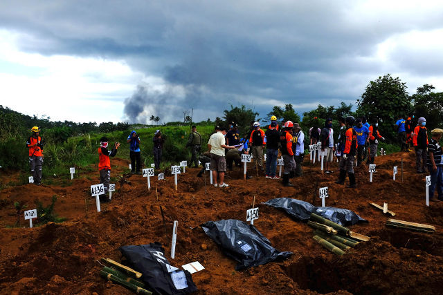MASS BURIAL. Smoke rises from the distance after an air strike by an F/A50Ph fighter planes as members of the Lanao del Sur Provincial Disaster Risk Reduction and Management Office bury 36 human and 4 animal remains in Maqbara, Papandayan, Marawi City on October 5, 2017. Photos by Bobby Lagsa/Rappler