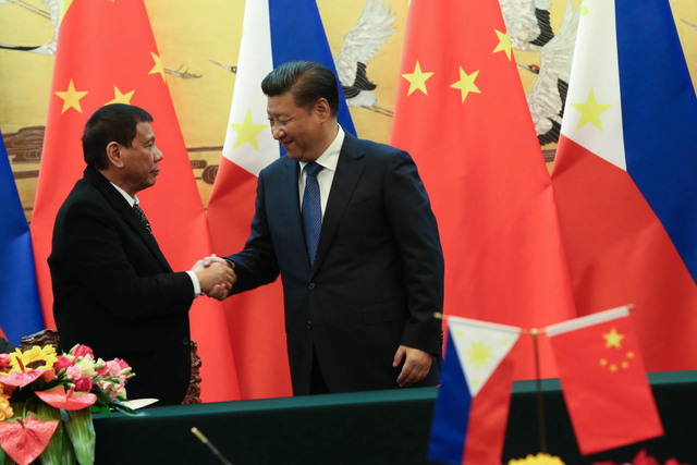 COOPERATING WITH CHINA. President Rodrigo Duterte shakes hands with President Xi Jinping during his state visit in October 2016. File photo by Toto Lozano/PPD
