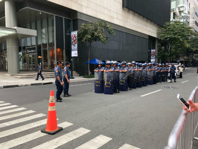 GUARDED. Police in riot gear surround nearby streets during Chinese President Xi Jinping's state visit.