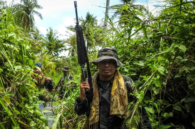 WADING INTO THE FRONT LINES. This photo taken on August 22, 2017 shows a government police officer along with members of the Moro Islamic Liberation Front (MILF-back) wading through a flooded farm on their way to the frontline in Datu Salibo town, Maguindanao province, in Mindanao. Photo by Ferdinandh Cabrera/ AFP