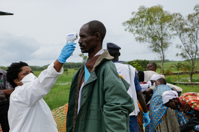 VIRUS CHECK. A medical staff member measures a man's temperature in Gatumba, Burundi, on the border with the Democratic Republic of Congo, on March 18, 2020. Photo by Onesphore Nibigira/AFP