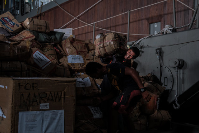 RELIEF GOODS. A volunteer carries relief goods for a waiting vehicle inside the deck of the BRP Davao del Sur. Photo by Bobby Lagsa/Rappler