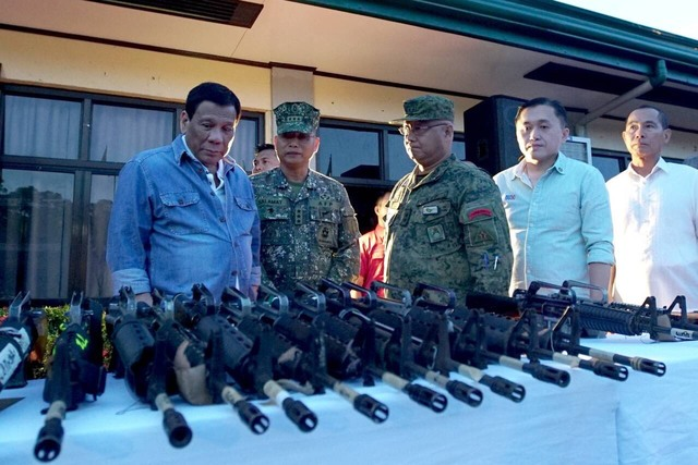 FRONTLINES. President Rodrigo Duterte inspects firearms surrendered by NPA members in Isabela. Malacañang photo