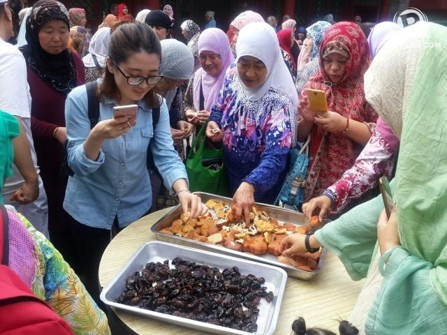KURMA. Pengurus masjid membagikan kurma dan makanan khas lainnya kepada umat Muslim usai menunaikan salat Idul Adha pada Senin, 12 September. Foto oleh Uni Lubis/Rappler