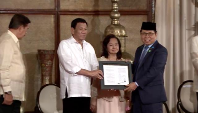 LANDMARK LAW. President Rodrigo Duterte presents the Bangsamoro Organic Law to Moro Islamic Liberation Front chairman Al Haj Murad Ebrahim on August 6, 2018. RTVM screenshot
