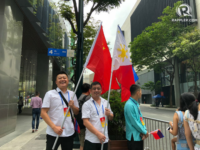 PH-CHINA FRIENDSHIP. Two men who are part of the group of Filipino Chinese awaiting Xi Jinping's arrival outside a Taguig City hotel hold the Chinese and Philippine flags to symbolize the two countries' friendship. All photos by Sofia Tomacruz/Rappler