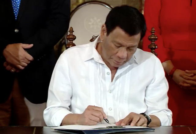 NEW LAW. President Rodrigo Duterte signs the national ID system law on August 6, 2018. RTVM screenshot