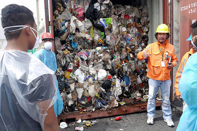 DUMPED IN THE PHILIPPINES. Environment officials open one of almost 100 container vans of garbage shipped illegally from Canada. Photo courtesy of BAN Toxics