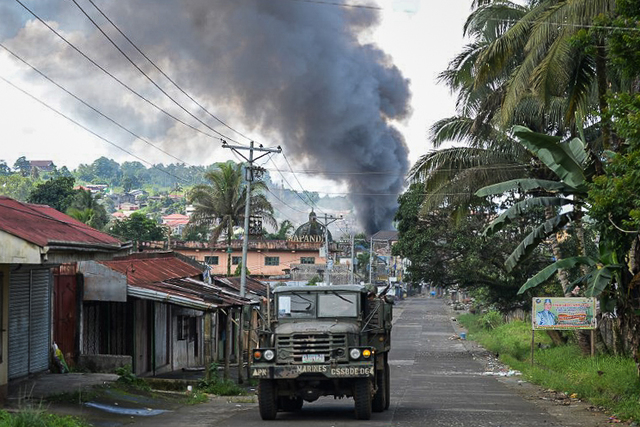 BURNED HOUSES. A Philippine Marines truck speeds away as black smoke billows from burning houses after military helicopters fired rockets at militant positions in Marawi on May 30, 2017. Photo by Ted Aljibe/AFP