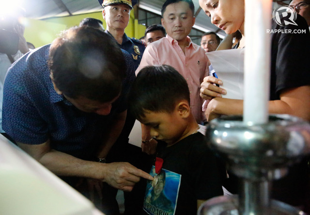 TRIBUTE TO A FATHER. President Rodrigo Duterte pins the Order of Lapu-Lapu Kalasag Medal onto the shirt of 6-year-old Jun Hilario. Presidential photo