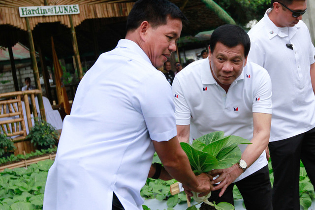 GUARDING THE PRESIDENT. President Rodrigo Duterte is assisted by Presidential Security Group (PSG) Commander Rolando Bautista during the launch of the PSG's vegetable garden program. File photo by Rey Baniquet/Presidential Photo