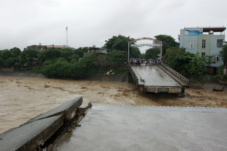 SEVERE FLOODING. This picture taken on October 11, 2017 shows residents standing at an end of a destroyed bridge in the northern province of Yen Bai. Photo from Vietnam News Agency/AFP