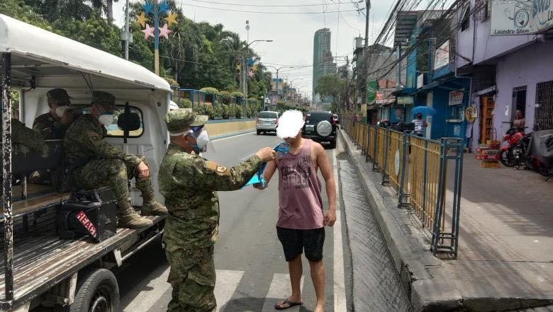SOLDIERS' PATROL. A Philippine Army reservist gives a Mandaluyong City pedestrian a face mask. Photo from the Mandaluyong CDRRMO