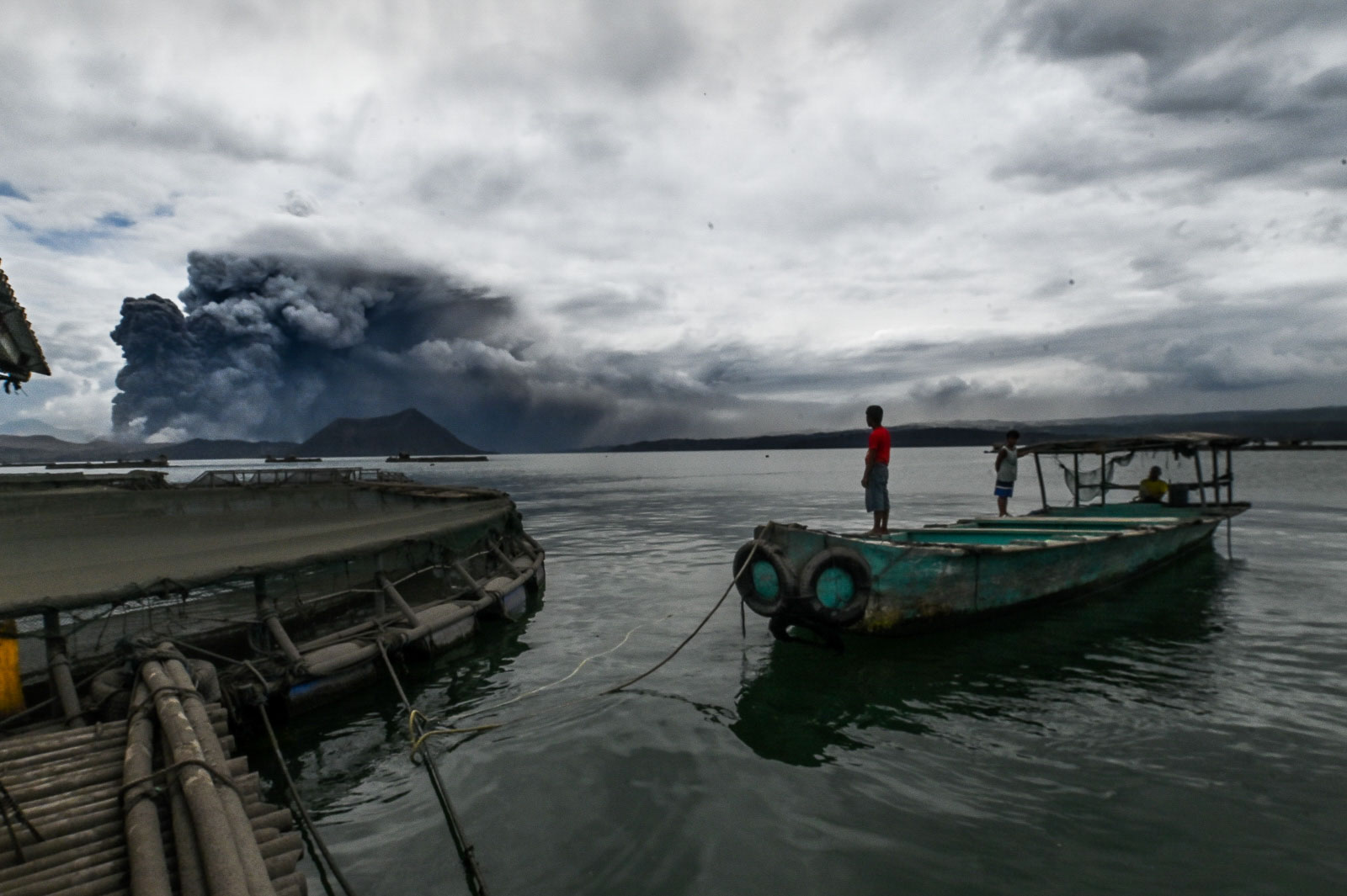 AWAKE. Fisherman Rolando Leanos watches from his boat in Laurel, Batangas, on January 13, 2020, as Taal Volcano spews ash. File photo by Alecs Ongcal/Rappler