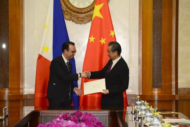 LETTER. Philippine Foreign Affairs Secretary Alan Peter Cayetano (L) shakes hands with Chinese Foreign Minister and State Counselor Wang Yi after he passed on a hand-written letter from President Rodrigo Duterte to Chinese President Xi Jinping during a meeting at the Diaoyutai State Guesthouse in Beijing on March 21, 2018. Photo by Parker Song/AFP