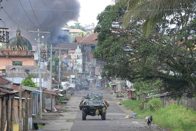 CONFLICT. A Philippine Marines armoured personnel carrier speeds away in Marawi on the southern island of Mindanao on May 30, 2017, as fighting rages on the eighth day. AFP PHOTO / TED ALJIBE