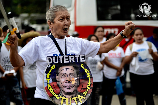 TARGET. A protester wears a dart board with the face of President Rodrigo Duterte as the target. Photo by Maria Tan/Rappler