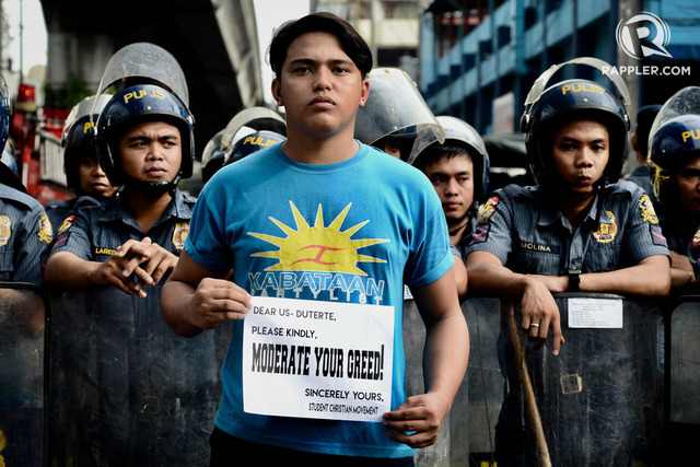 "YOUTH. A member from the Kabataan Party list stands in front of the police barricade with a message to the President that read ""Moderate Your Greed!"" Photo by Maria Tan/Rappler"