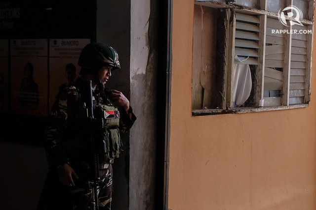 MARAWI CLASHES. A soldier checks on his fellow soldiers over the radio as he holds his post inside Marawi City on June 22, 2017. File photo by Bobby Lagsa/Rappler