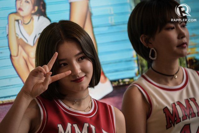 K-POP STARS. Nancy gets playful as Hye Bin listens on at their press event.