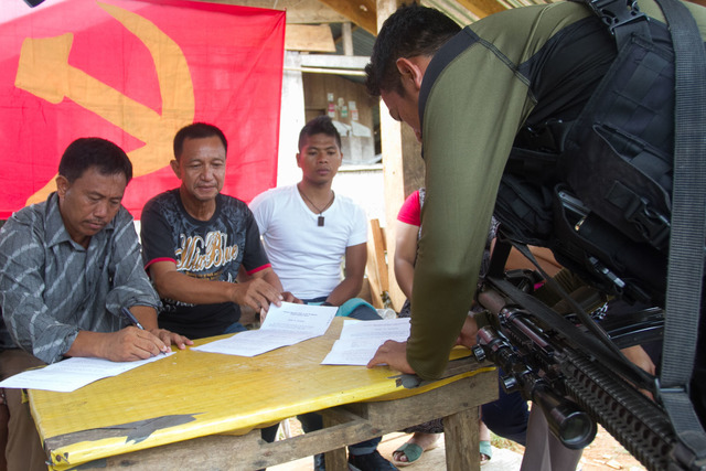 RELEASED. PO1 Alfredo Basabica Jr. (in white shirt) looks on as, an NPA guerilla and village officials from Cateel, Davao Oriental, sign his release papers in Barangay Binondo, Baganga town, Davao Oriental on July 28, 2017. All photos by Manman Dejeto/Rappler