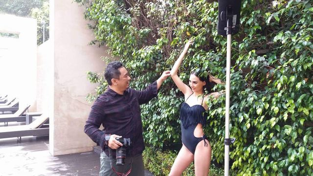 POSE. Raymond Saldaña instructs one of his models during a photo shoot session.