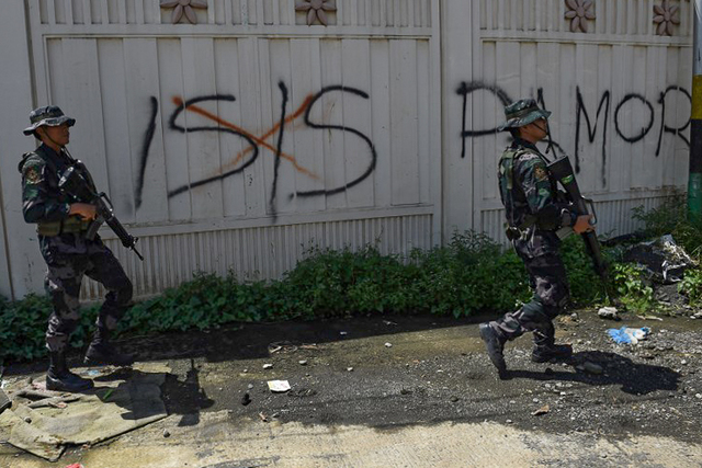 Soldiers walk past Islamic State (IS) group graffiti in Marawi on on May 31, 2017. Photo by Ted Aljibe/AFP