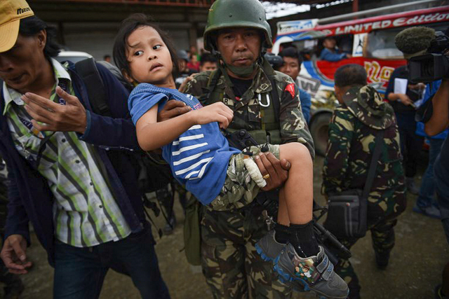 RESCUING CIVILIANS. A soldier carries a child during rescue and evacuation operations in Marawi on May 31, 2017. Photo by Ted Aljibe/AFP